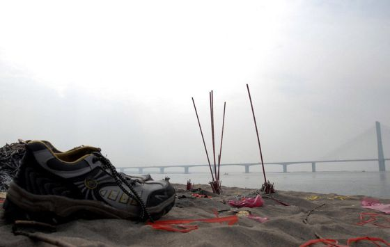 A pair of shoes and unfinished incense sticks left by the riverside.