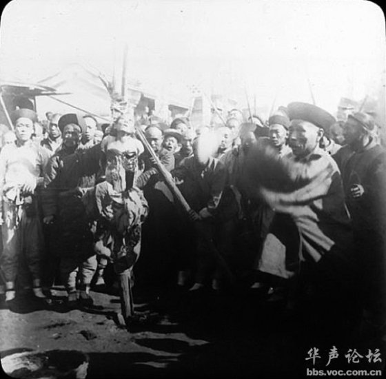 A female criminal strung up surrounded by onlookers during late Qing China