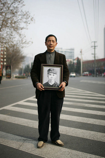 Chinese war veteran Guo Yimin holds a portrait of his old Sino-Vietnamese War buddy