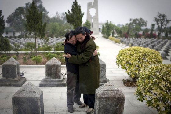 Guo Yimin embraces and cries with another war veteran at the Guangxi martyrs cemetary