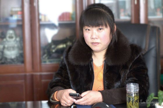 Asian female boss wearing fur coat.