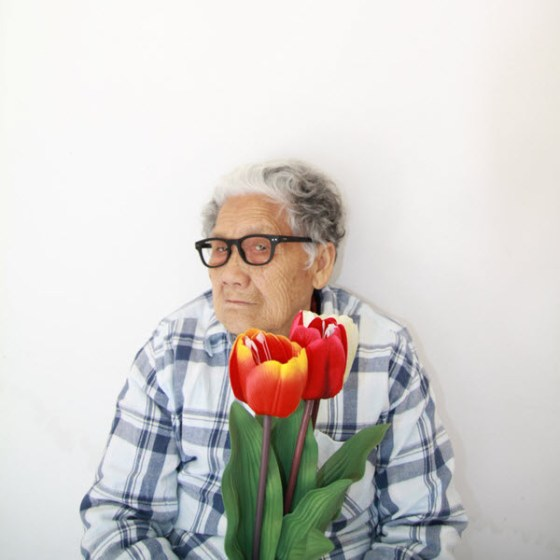 Crazy Chinese granny holding two red flowers.