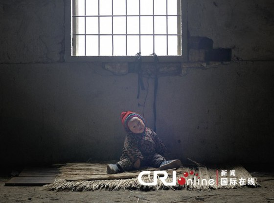 A child tied to a window with a rope at a brick factory in Zhejiang China.
