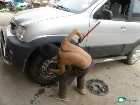 A small Chinese boy removes lug nuts from a car.