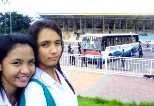 Two Filipino schoolgirls taking photos in front of the Hong Thai Travel tour bus where Hong Kong tourists were held hostage and killed.