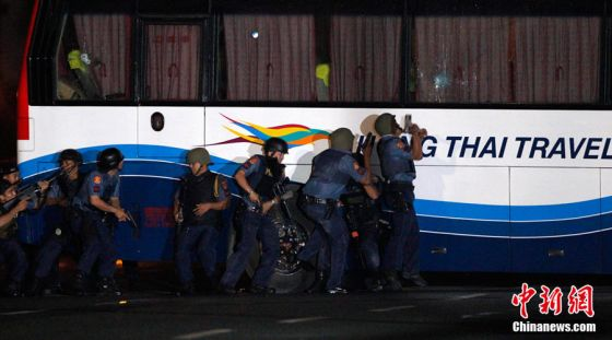Police commandos surround a bus with tourists being held hostage at Quirino Grandstand in Manila August 23, 2010. Police were poised to storm a bus where a sacked former Filipino policeman was holding 15 Hong Kong tourists hostage in downtown Manila after shots were heard at the scene, TV pictures and a Reuters witness said. REUTERS/Erik de Castro
