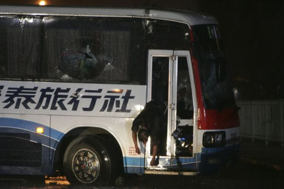 A body hangs from the glass door of a tourist bus following an assault by police and SWAT members to rescue hostages at Manila's Rizal Park Monday Aug.23, 2010 in Manila, Philippines. Former Senior Inspector Rolando Mendoza, a dismissed policeman armed with automatic rifle, seized the bus in Manila Monday with 25 people aboard, mostly foreign tourists in a bid to demand reinstatement, police said. Mendoza was killed along with an undetermined number of hostages. (AP Photo/Bullit Marquez)