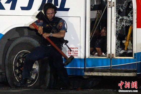 A police commando tries to break down the door of a bus as a body lies inside during the assault on a bus with tourists being held hostage at Quirino Grandstand in Manila August 23, 2010. Philippine police commandos crouched around a bus where a sacked former policeman was holding 15 Hong Kong tourists hostage in Manila on Monday and shots were heard at the scene, TV pictures and a Reuters witness said.  REUTERS/Erik de Castro