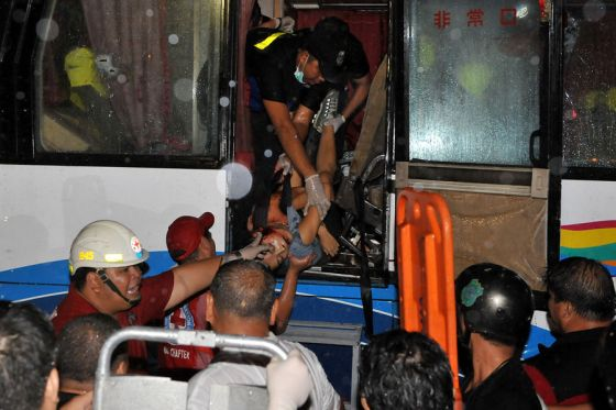 Paramedics (top) lower a victim from the hijacked bus in Manila on August 23, 2010.  The gunman who seized a bus carrying Hong Kong tourists killed at least four of his hostages in the Philippines, doctors said.    AFP PHOTO / JAY DIRECTO