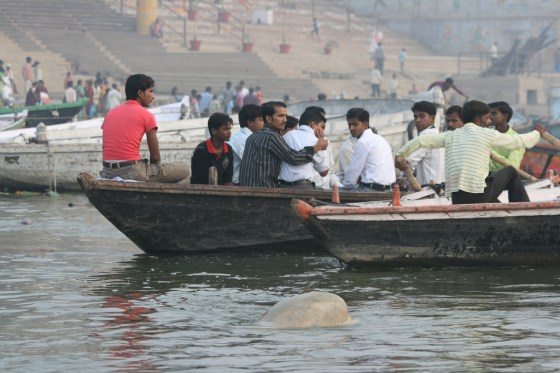 A dead body floats in the river as Indians in a boat pass by.