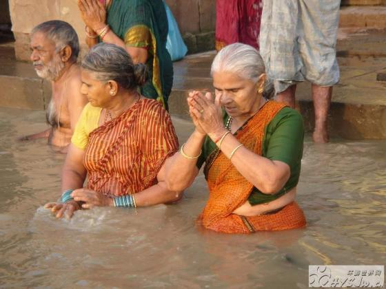 Indian women bathing and praying in the Ganges River.