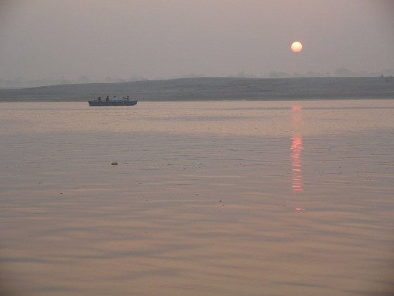 Sunset over the Ganges River, a corpse floats in the water.