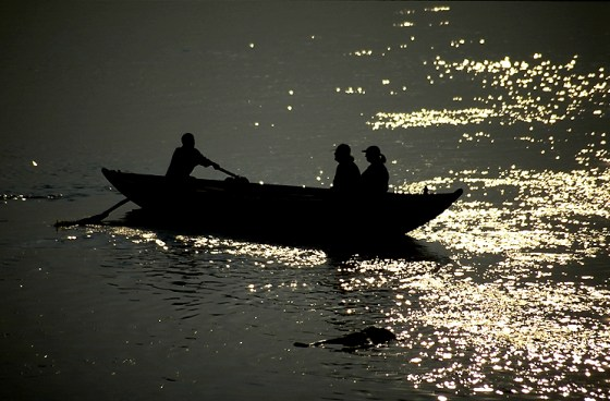 Dusk on the Ganges River, a corpse floats in the water.