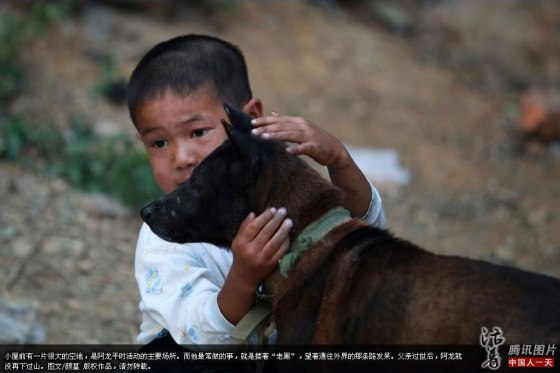AIDS orphan A-Long pets his dog, Old Black.