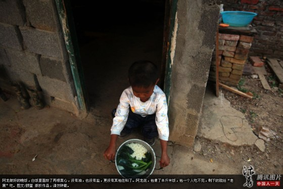 AIDS orphan A-Long shows his pot of plain white rice and vegetables that he cooked himself for his dinner.