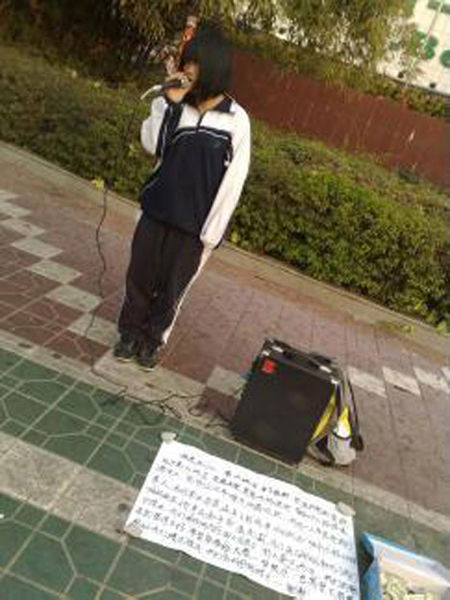 February 8th afternoon at 5 o'clock, in front of the A.Best supermarket at Shatoujiao, a young teenage girl sells songs for money.