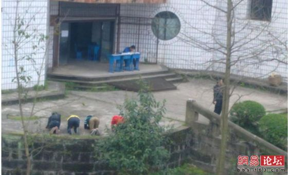 Chinese students being punished to kneel on the ground and write self-criticisms while the teacher relaxes and smokes beside them.