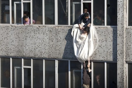 Men on the 6th and 7th floors of this Changchun residential building struggle to safely rescue a bride who had just tried to commit suicide by jumping off the 7th floor.