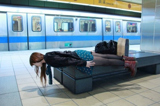 A young woman in Taiwan lies rigid over the corner of a subway station bench.