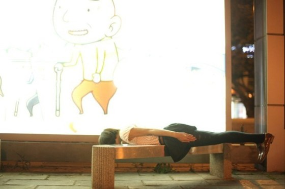A young girl lies rigidly face down on a bench in Taiwan.