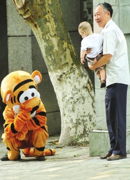 A man in a Tigger costume waves at a zoo visitor in Chengdu, China.