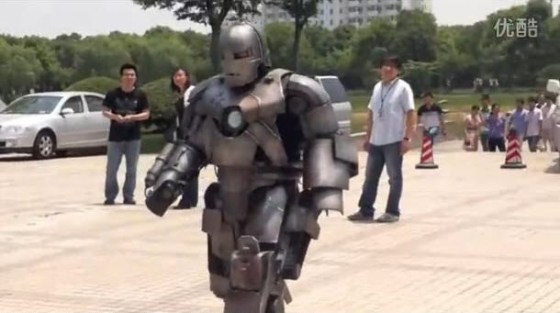 A Chinese man walking around in a self-made MK I Iron Man Armor suit.