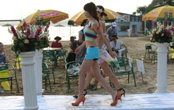 Chinese women walk down a runway in swimwear at a matchmaking event for rich Chinese men in Wuhan.