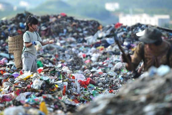 A little Chinese girl helping her parents scavenge a Guiyang garbage dump for salvage and recyclables.