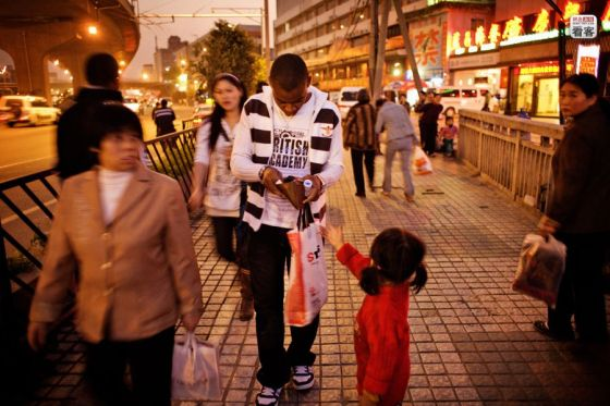An African on the streets of Guangzhou giving some money to a child beggar.