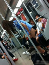 A young Chinese girl changing clothes on the Shanghai subway.
