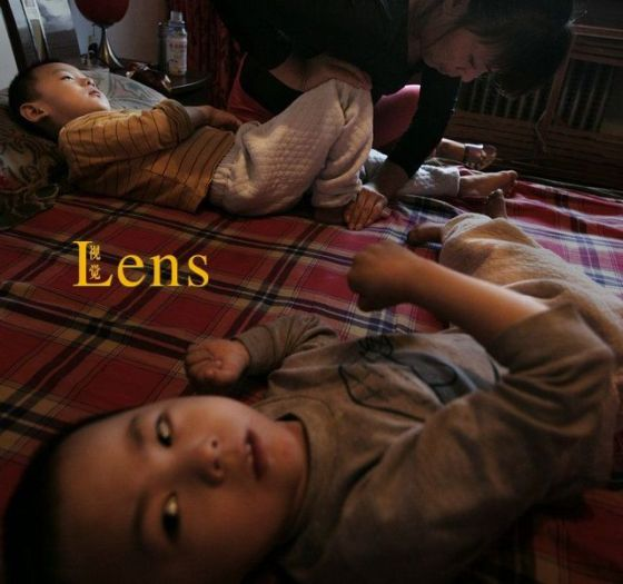 Several foster children in China lying on a bed.