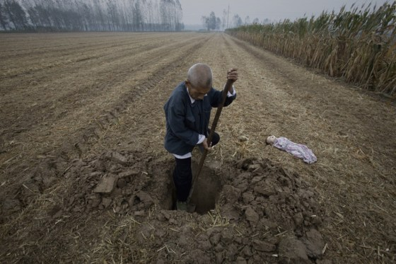 An old Chinese man burying a dead baby in a field.
