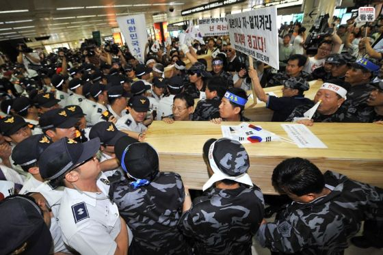 Korean nationalists carry coffins into Gimpo Airport to protest Japanese officials visiting islands disputed between the two countries.
