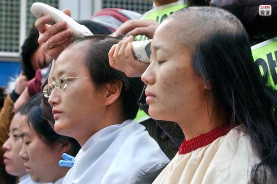 Korean women demanding the annulment of an old law by shaving their heads.