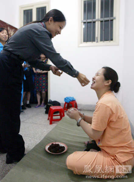 A female prison guard feeds a condemned inmate on death row a lychee.