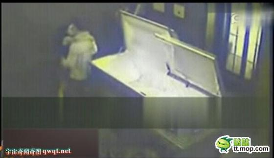Couple caught passionately kissing beside a coffin.