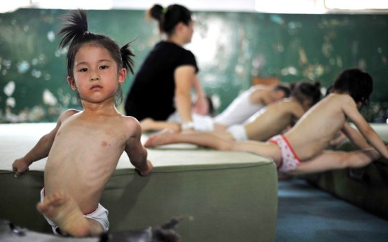 Little Chinese girls practicing the splits for gymnastics.