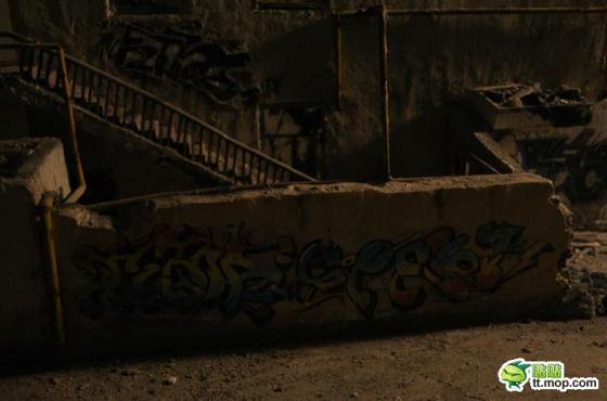 A dark and gritty alley with walls covered in graffiti.