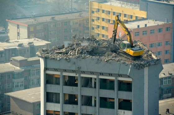 A lone excavator digger working on the roof of a 12 story building in Taiyuan, Shanxi province, China.