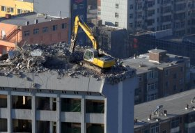 A lone excavator digger working on the rooftop of a 12 story building in Taiyuan, Shanxi province, China.