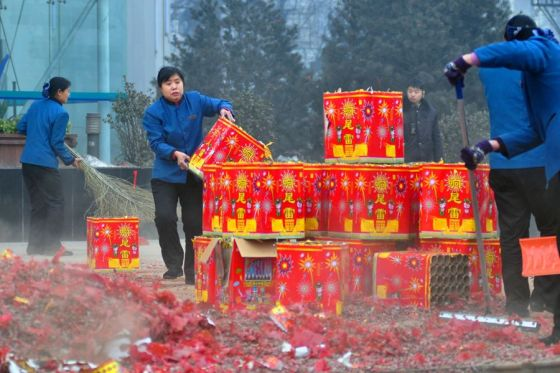 Chinese women cleaning up the streets of used fireworks and firecrackers.