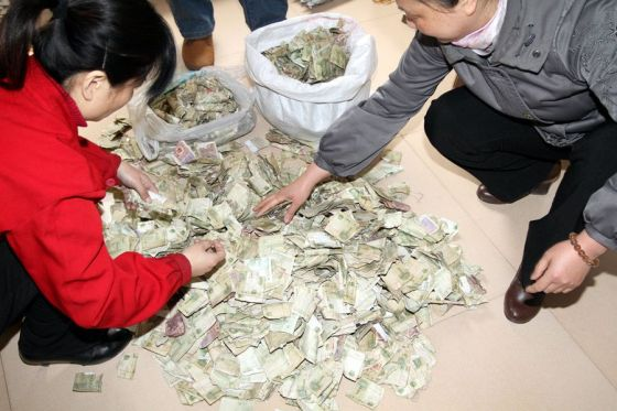 Employees of a Henan public bus company sort through a pile of 1 RMB cash bills in preparation for paying worker wages because the bank refuses to accept such small change.