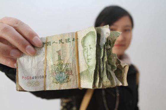 Damaged 1 RMB cash notes that bus riders have deposited as fare in Henan province.
