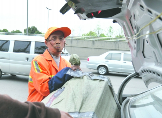 A Chinese sanitation worker returns one of 9 boxes of goods lost by Wang Hongjun.