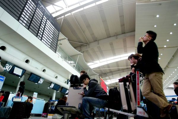 Delayed airline passengers grounded at Dalian Airport due to foggy weather conditions.