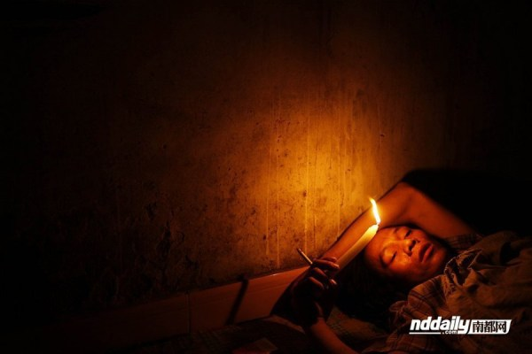Wu Guilin holding a lit candle as he falls asleep.