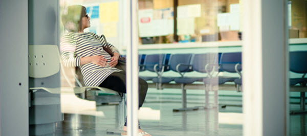 Pregnant Chinese mother in a hospital waiting room.