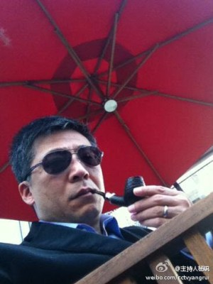 CCTV International presenter Yang Rui smoking pipe under red canopy.
