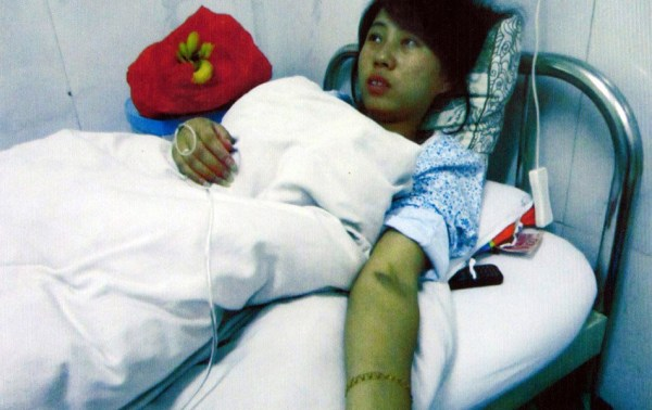 Feng Jianmei lying on a hospital bed. For violating China's One-Child Policy, local family planning officials forcibly terminated her 7-month pregnancy and induced labor to remove the dead baby.