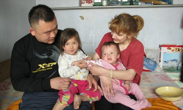 Xu Shuai and his British wife Joanne Margaret Noble sit at home with their two children on May 2 in Weifang, Shandong Province.